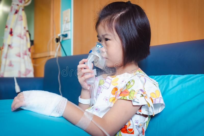 Sad asian child holds a mask vapor inhaler for treatment of asthma. royalty free stock image