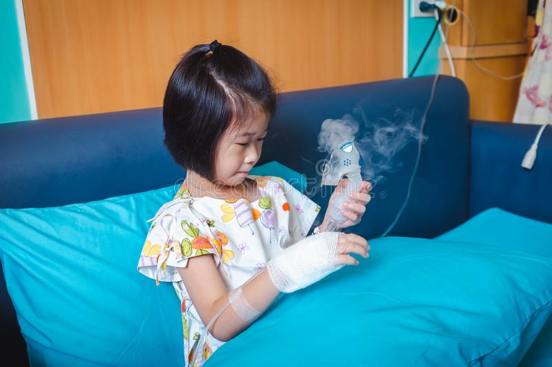 Sad asian child holds a mask vapor inhaler for treatment of asthma. stock photos