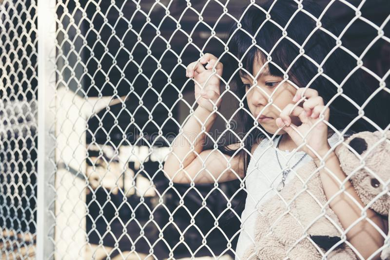 Sad Asian girl child alone in cage was imprisoned make no freedom or lack of freedom. Violence family concept royalty free stock image