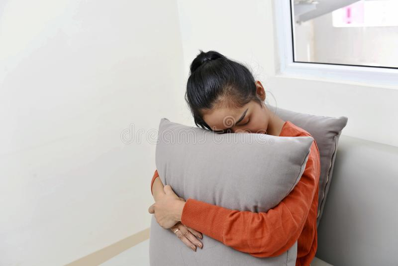 Sad asian woman hugging a pillow and sitting on sofa royalty free stock photography