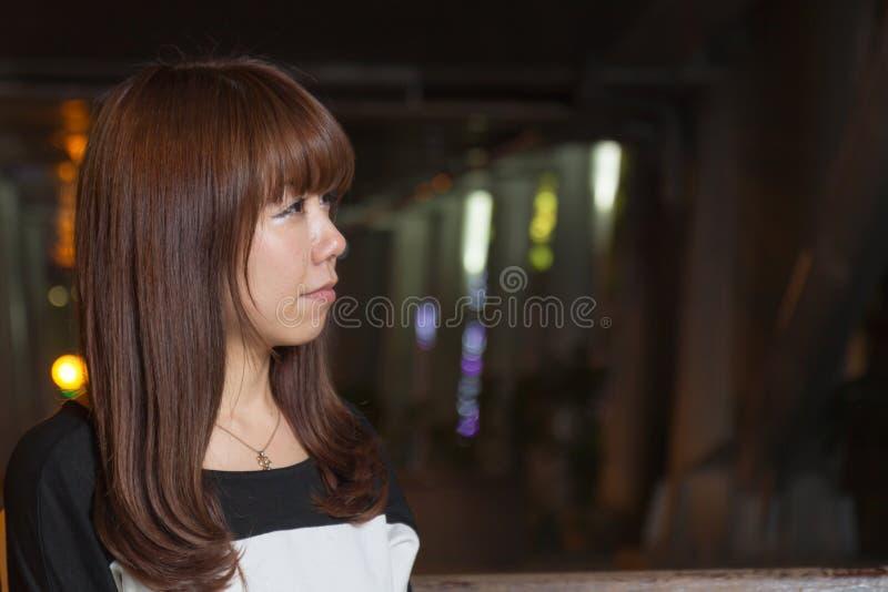 Sad Asian Woman on a Park Bench stock image