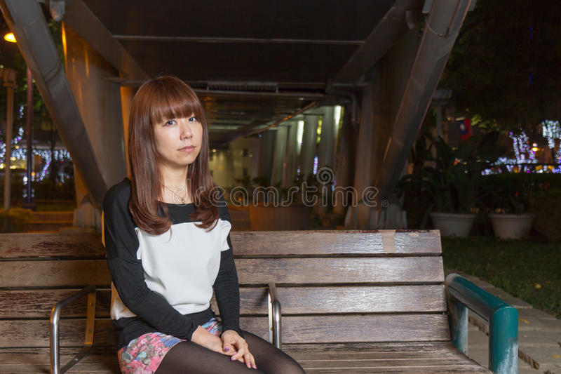 Sad Asian Woman on a Park Bench royalty free stock image