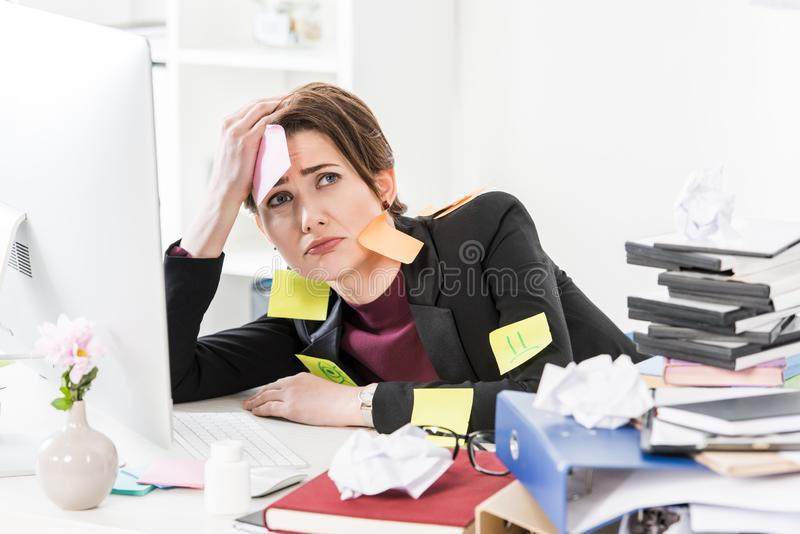 Sad attractive businesswoman sitting with stickers on face and clothes stock images