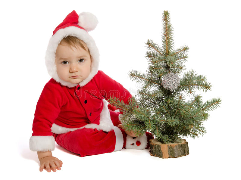 Sad baby in Santa Claus clothes with xmas tree. On white background stock photography
