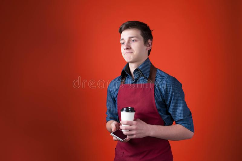 Sad barista with dark hair in burgundy apron holding paper cup and smartphone on orange background. Handsome sad barista with dark hair in burgundy apron holding royalty free stock photo