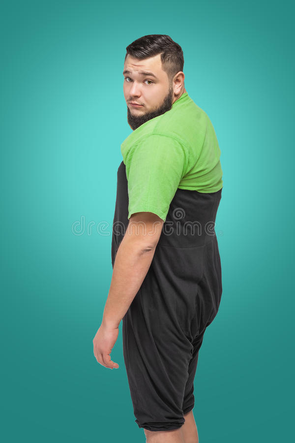 Sad bearded fat man in black bloomers. Tired upset man in green shirt and black pants over turquoise background royalty free stock images