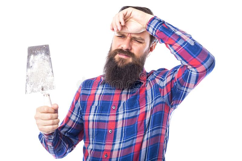 Sad bearded man holding used masonry tools isolated on white stock image
