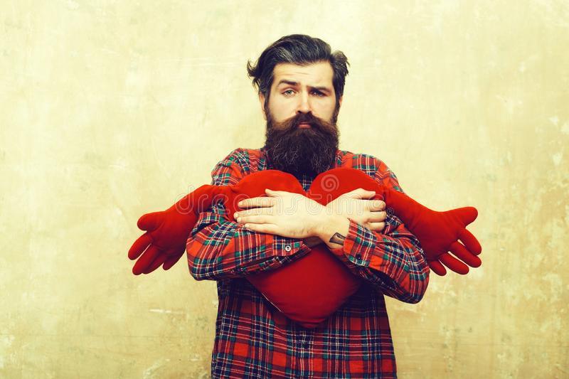 Sad bearded man hugging red heart shape toy with hands royalty free stock photography