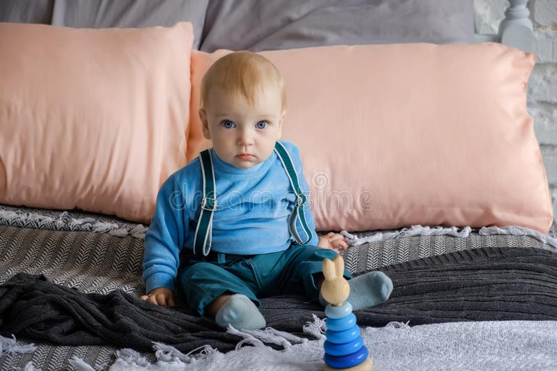Sad, but beautiful blue-eyed baby sitting on the bed next to the toy pyramid.  stock images