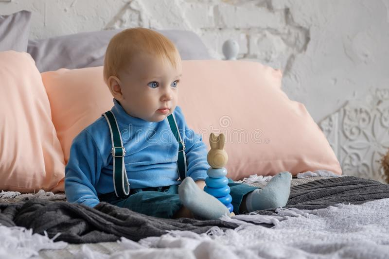 Sad, but beautiful blue-eyed baby sitting on the bed next to the toy pyramid.  royalty free stock photography