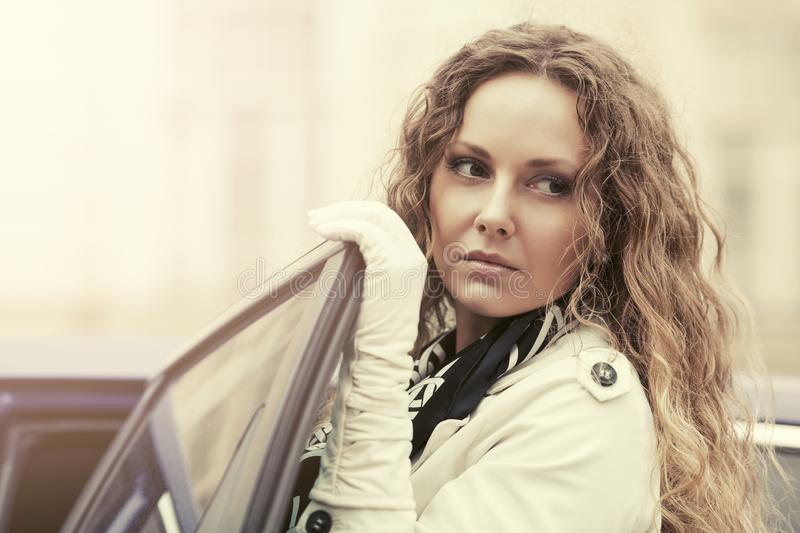 Sad beautiful fashion woman in trench coat next to her car royalty free stock photography