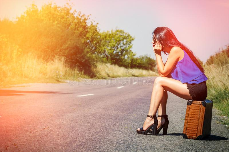 Sad beautiful girl traveler with suitcase on road, hitchhiking. Concept of travel, adventure, vacation, freedom. Waiting for car o. R bus royalty free stock images