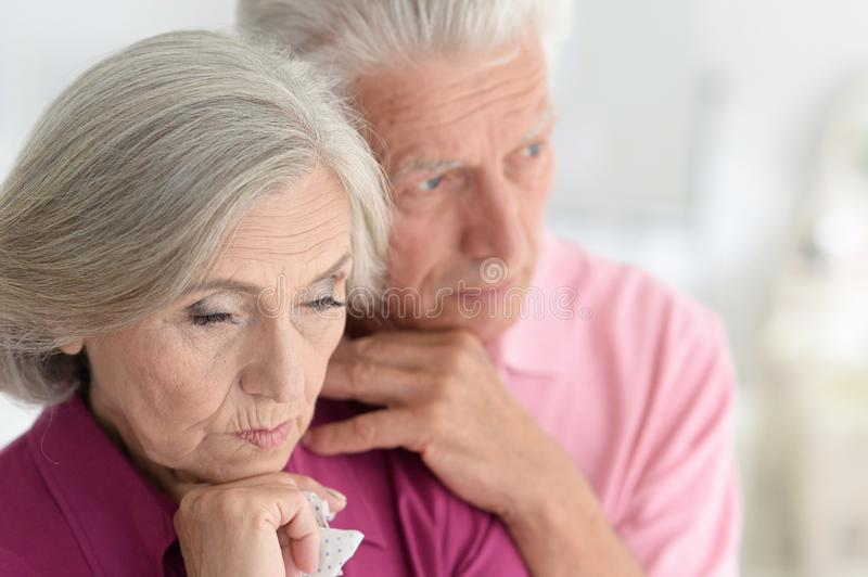 Sad Senior couple at home hugging royalty free stock photo