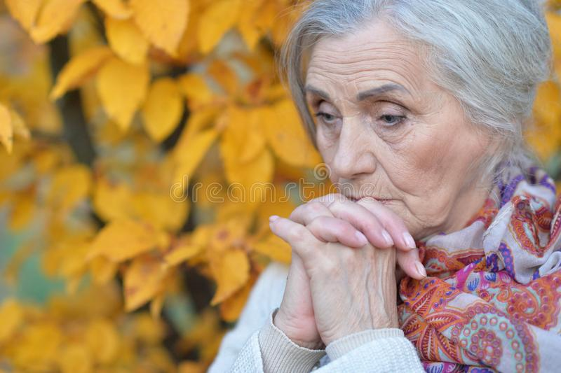 Close up portrait of sad senior woman in autumn park royalty free stock photos