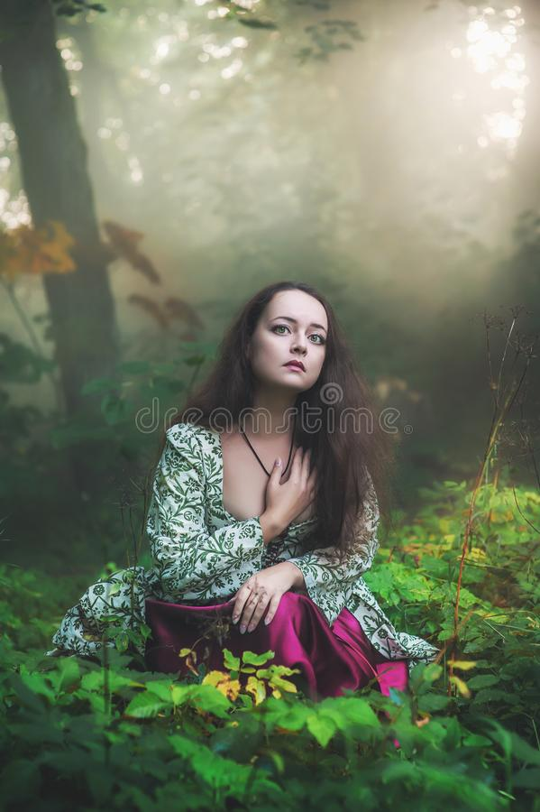 Sad beautiful woman in medieval dress sitting in grass. Outdoor stock image