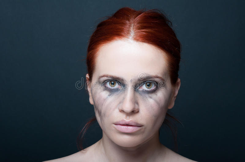 Sad beautiful woman with smudged make-up royalty free stock photography