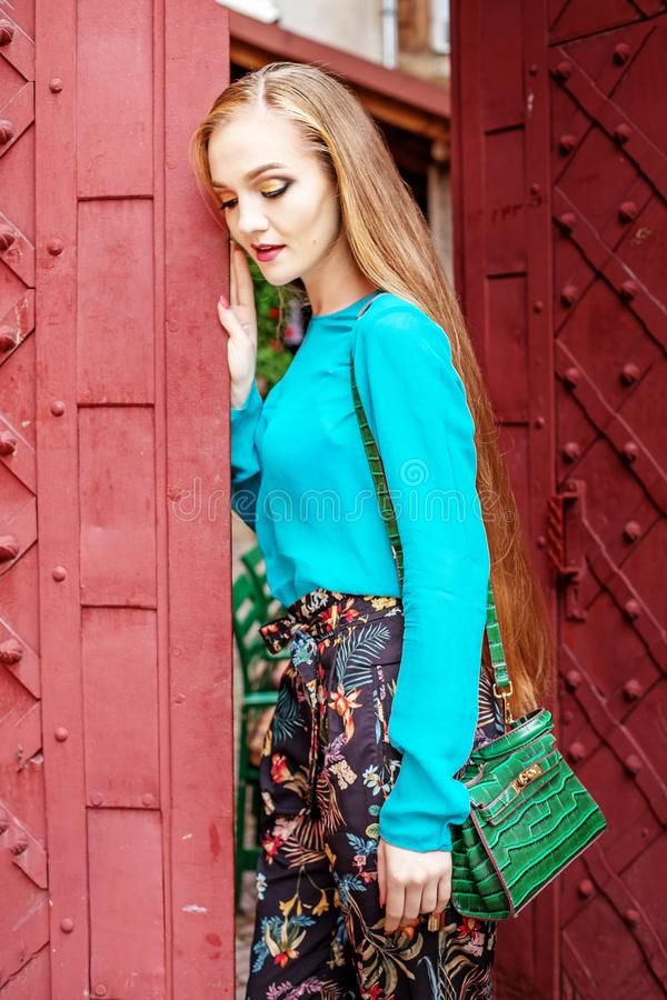 Sad beautiful woman standing near the gate. The concept of lifestyle and urban. stock photography