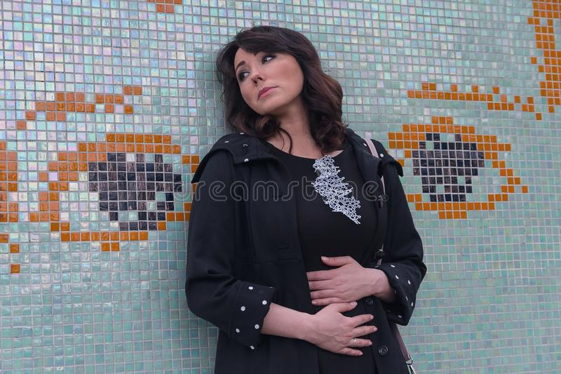 Sad beautiful woman by the wall royalty free stock photography