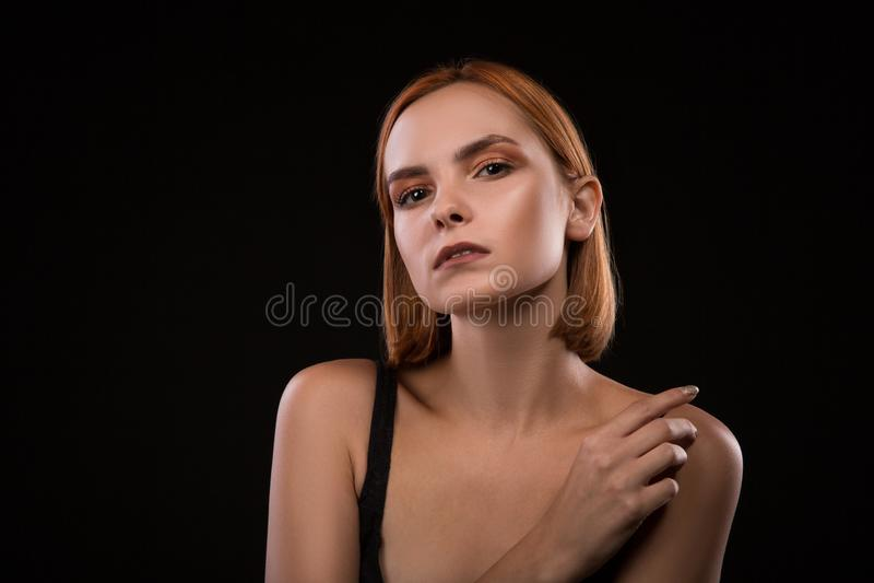 Sad blond woman portrait against black background stock photo