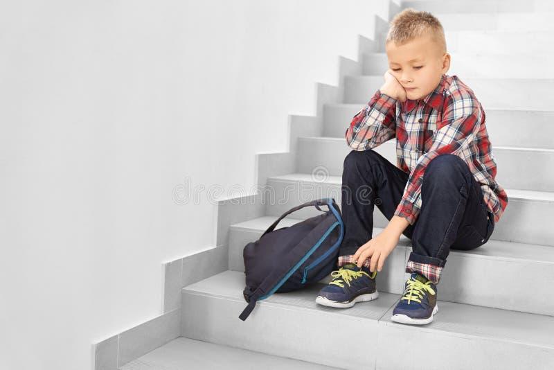 SAD blonda skolapojkar som bara sitter på trappa royaltyfri foto