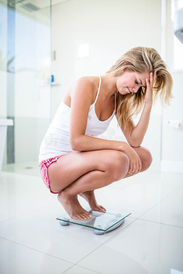Sad blonde on weighting scale stock image