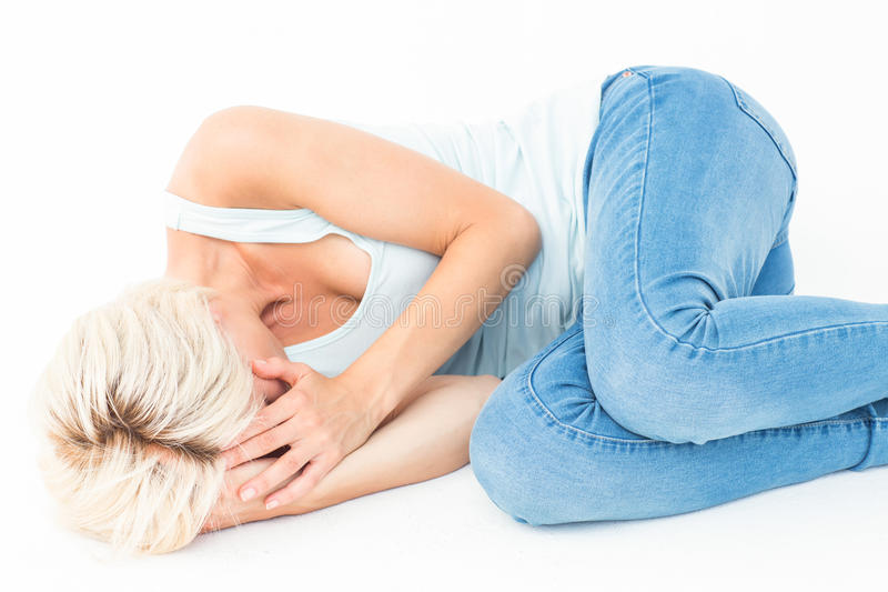 Sad blonde woman lying on the floor. On white background royalty free stock photos