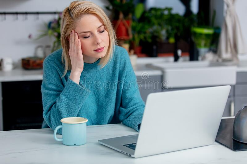 Blonde woman with notebook computer sitting at kitchen. Sad blonde woman with notebook computer sitting at kitchen royalty free stock images