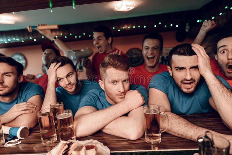Sad blue team fans at bar in sports bar with red team fans celebrating and cheering in background. They are watching football game royalty free stock photography