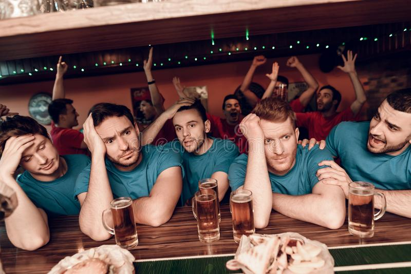 Sad blue team fans at bar in sports bar with red team fans cheering in background. They are watching football game stock image