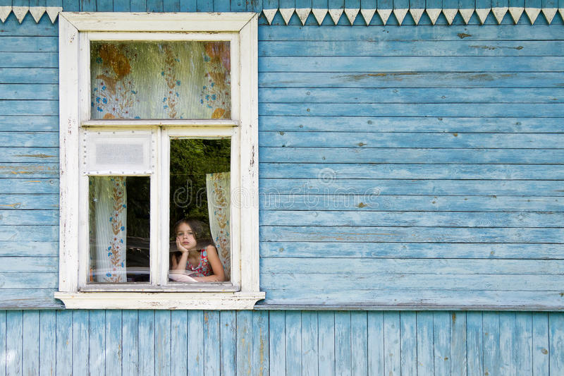 Sad bored little girl looking out the country house window leaning her face on her hand stock images