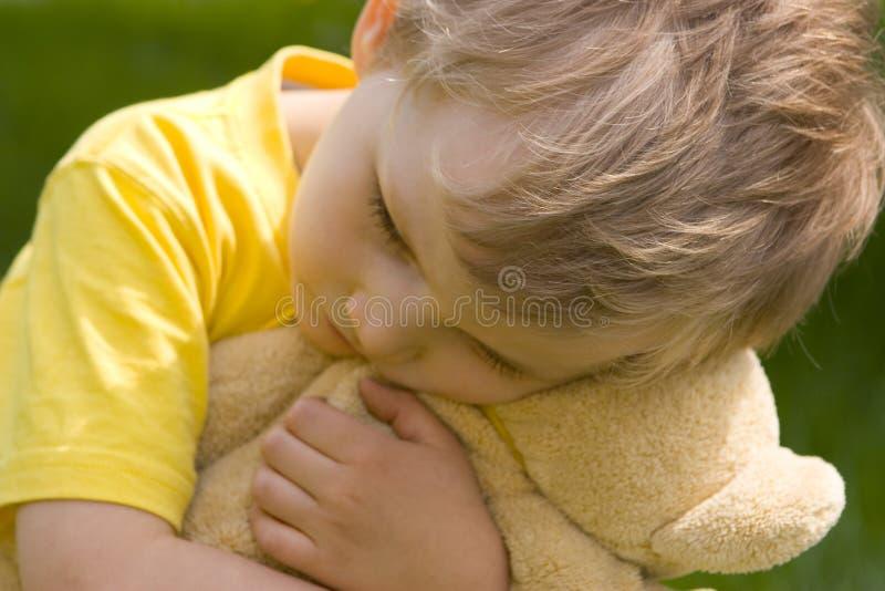Sad boy. Boy with bear--soft focus royalty free stock image