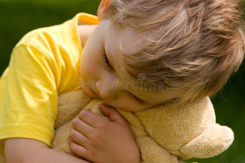 Sad boy. Boy with bear--soft focus royalty free stock photo