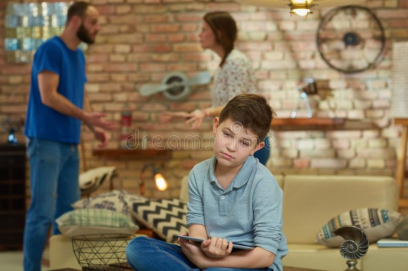 Sad boy arguing parents. Sad boy sitting on sofa with tablet while parents shouting, arguing at background royalty free stock photo