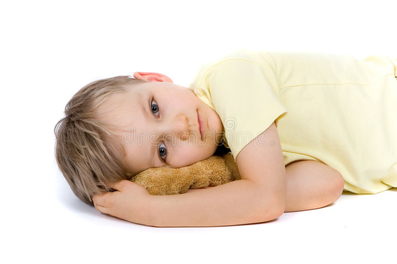 Sad Boy With Bear. Sad little boy laying on his side on the floor with his toy stuffed bear cuddled up under his face. Taken in studio isolated on white royalty free stock photography