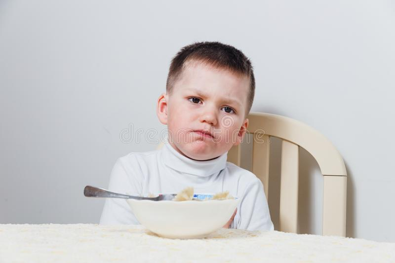 Sad boy does not want to eat. Sad little boy does not want to eat royalty free stock photos