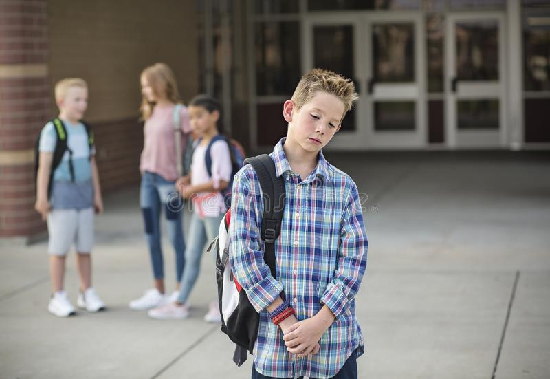 Sad boy feeling left out, teased and bullied by his classmates stock photo