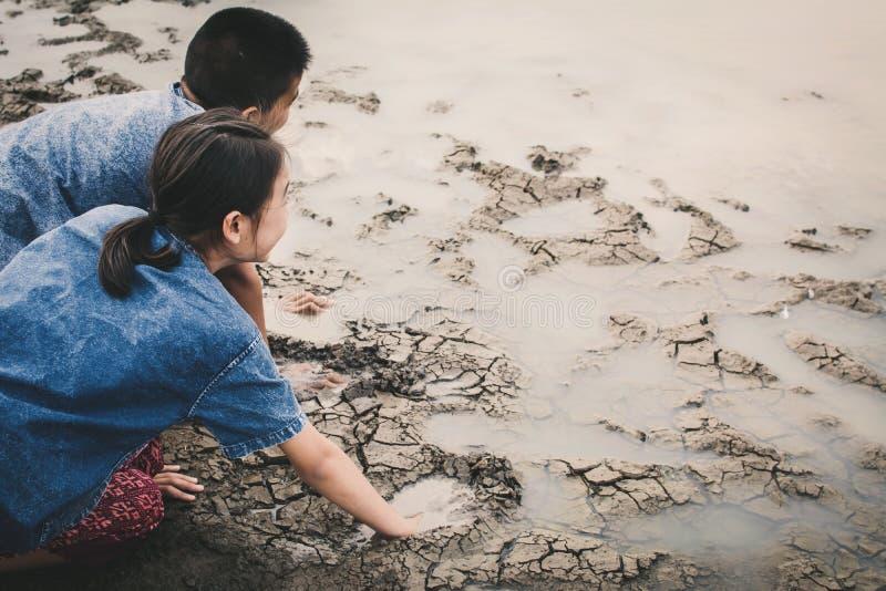 Sad boy and girl praying for the rain on lake stock photo