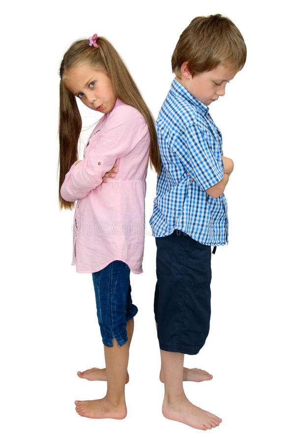 Sad boy and girl punished after argument, on white. Sad kids at odds with each other, after argument or quarrel, look down - shot isolated on white background royalty free stock photo