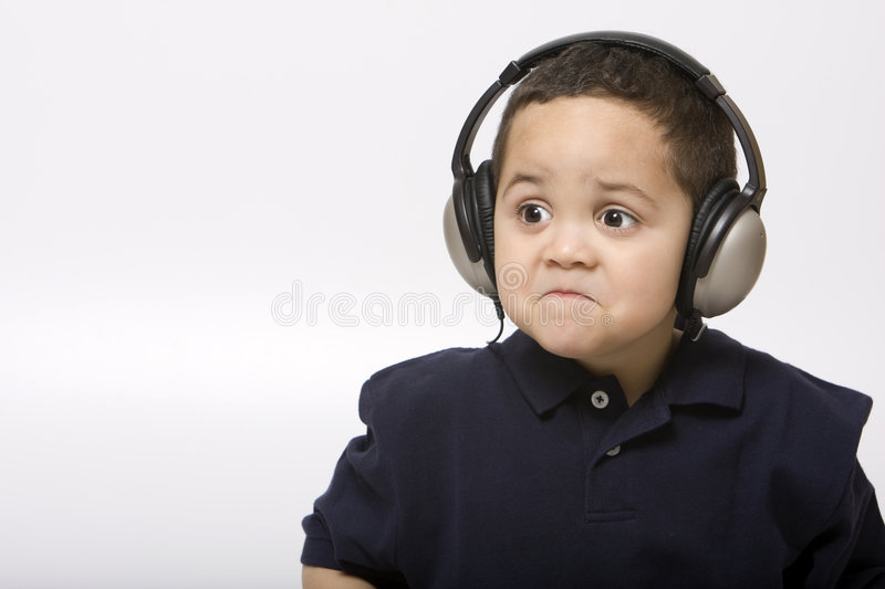 Sad boy with headphones. Not liking song choice royalty free stock photo