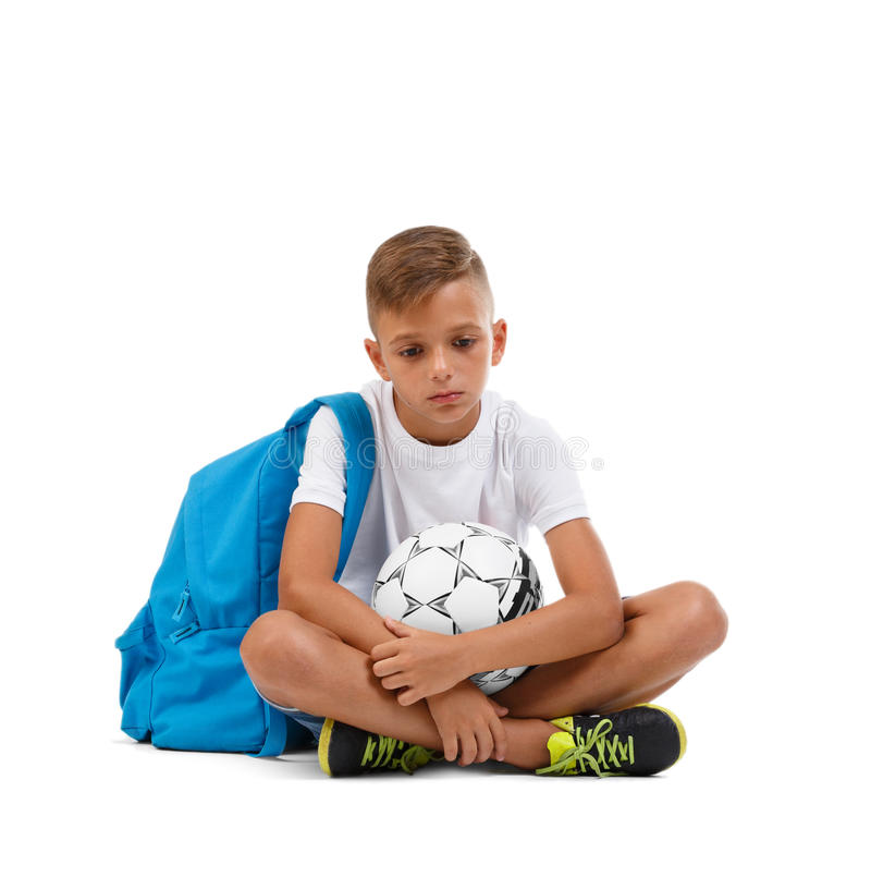 A sad boy isolated on a white background. Tired kid with a bright satchel and a soccer ball. A sitting child. Copy space. An upset boy sitting on the ground in a royalty free stock images