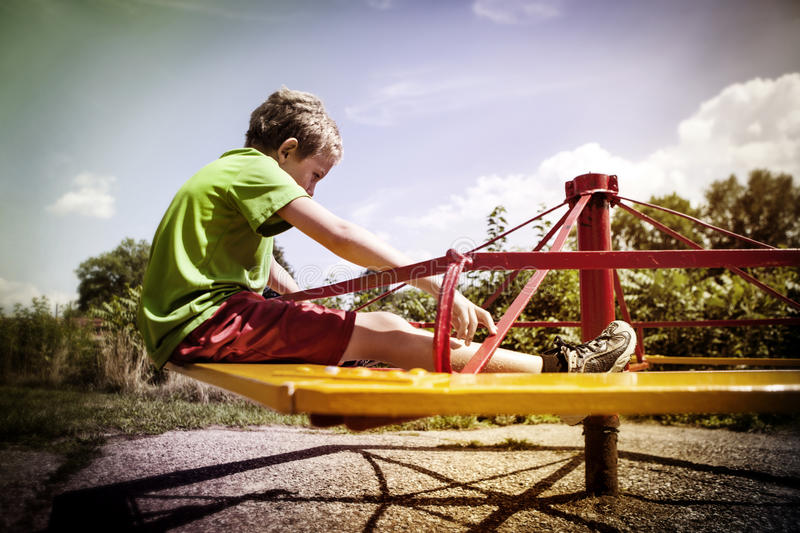 Sad boy on a merry go round. A boy is sitting on the merry go round at a park stock photos