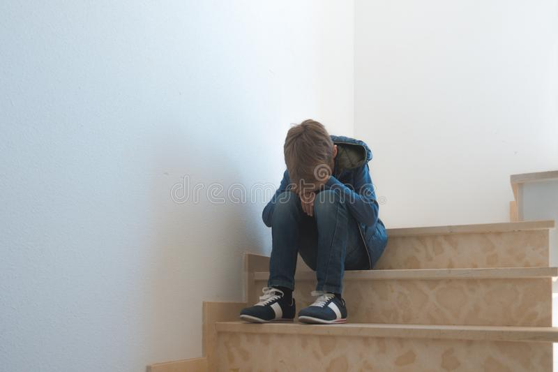 Sad boy sitting alone in the corner in the staircase. Sad alone boy sitting in the corner in the staircase stock photo