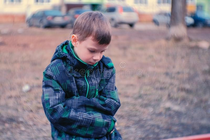Sad boy sitting on a bench. Boy is lost and waiting for parents. Sad boy sitting on a bench. Boy is lost and waiting for parents royalty free stock photography
