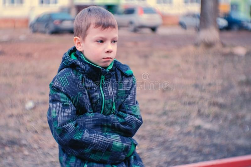 Sad boy sitting on a bench. Boy is lost and waiting for parents. Sad boy sitting on a bench. Boy is lost and waiting for parents royalty free stock images