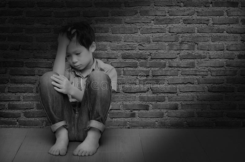 Download sad boy sitting on the floor stock photo image of black background