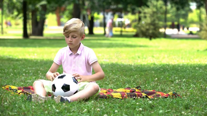 Sad boy sitting lonely in park, playing with football alone, bullying problem. Stock photo royalty free stock images