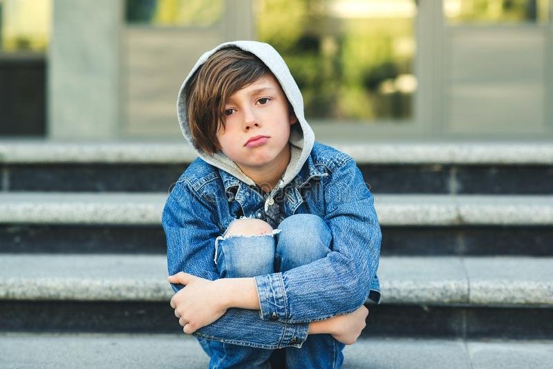 Sad boy is sitting on the stairs, before school. Alone unhappy child in city street. Bullying, depression, child protection or stock photo
