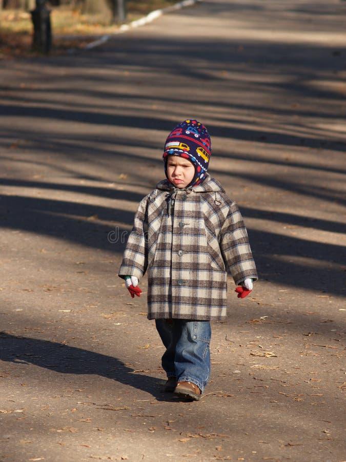 Sad boy walking stock images