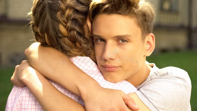 Sad boyfriend embracing teen girlfriend and looking into camera, difficulties. Stock photo royalty free stock image