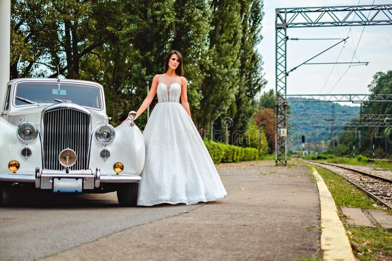 Sad bride standing by the classic car royalty free stock image
